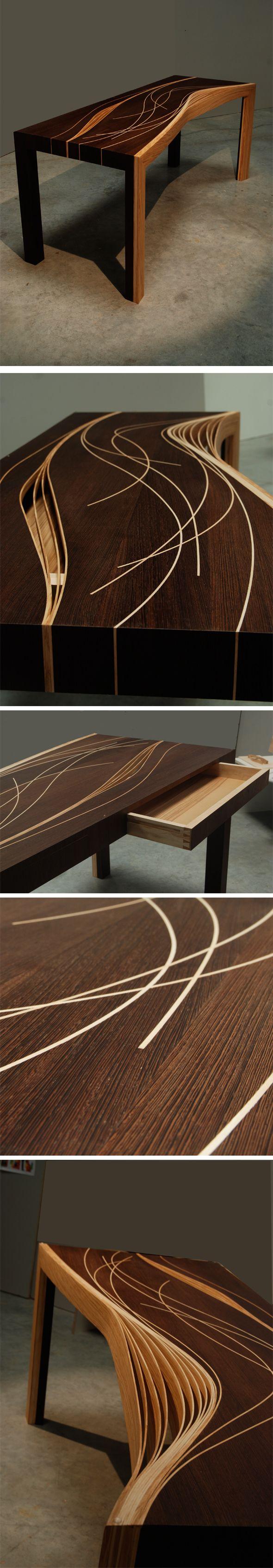 Bureau en bois de frêne réalisé par Aurélien Fraisse pour son diplôme de fin d'études. Il a découpé un plateau de frêne en fines lamelles, puis les a courbées pour donner la structure du plateau et du piétement. Il est constitué de deux tiroirs et d'un plateau en verre.