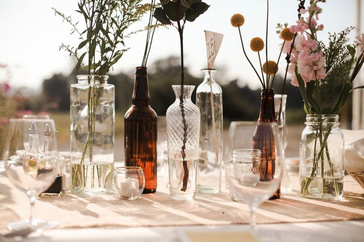 Vintage and mismatched bottles with various flowers for an eclectic touch