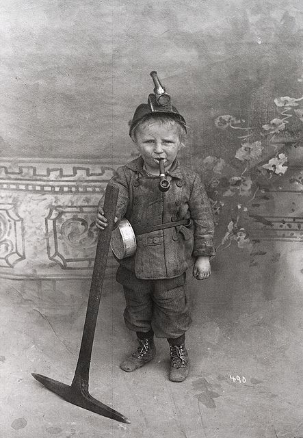 "Miner Boy. 'Children were cheap labor in the mines. This boy spent 10 hours a day in that outfit with only the light from his tallow wick lamp. He cleaned, and played the part of a ""canary,"" kids being easier to replace than good miners. He was probably Finnish or Swedish, and indentured to a mining company in Utah or Colorado in order to help pay off his father's debts.'"