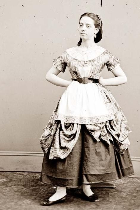 Woman c. 1855-65  (The hiking up of the over-skirt underneath the apron was to protect it while working - when company unexpectedly knocked at the door, down it went, like she was all put together!)