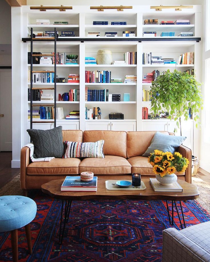 white built-ins + brass sconces + caramel leather sofa + a bright kilim = yes please.