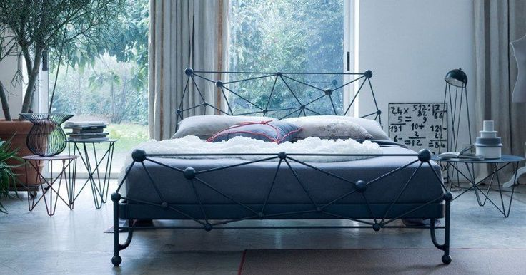 tête de lit originale en fer forgé bleu foncé, literie assortie et mobilier métallique design