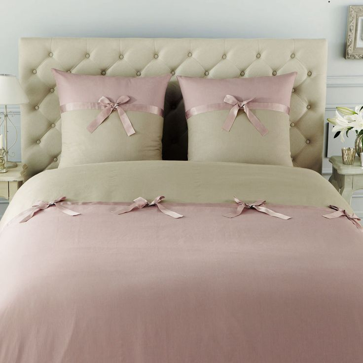 Uniformly beautiful pink and tan bedding with sweet bows on pillows
