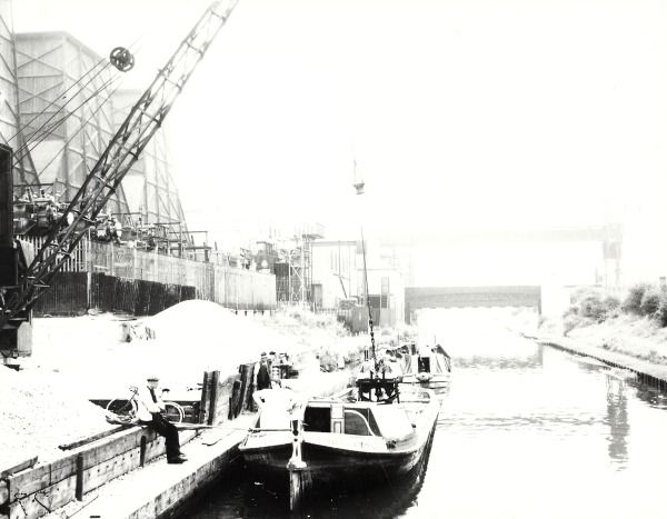 """Caption """"Black and white photograph showing the H Sabey & Co Limited wide-boat """"Southwold"""" and a pair of narrowboats moored outside the factory. Beside the canal there is a crane with its grabber in the hold of """"Southwold"""". A boatwoman is stood at the stern of """"Southwold"""" and there are people beside the canal. There are factory buildings running alongside the canal and a bridge visible in the distance."""""""