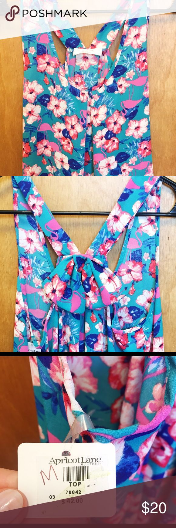 Cute Apricot Lane Flamingos/Floral Bow Top- NWT This is a never worn, Apricot Lane tank with flamingo and floral print and cute bow detail in the back. It still has the tags attached. It's a size medium, and it's a little too big on me that's why it's never been worn. Perfect for summer! ✅ Bundle and SAVE ❌ Sorry, no trades 🚛 Fast shipping 🚫Smoke and pet free home 💟 Happy Poshing! Tops Tank Tops