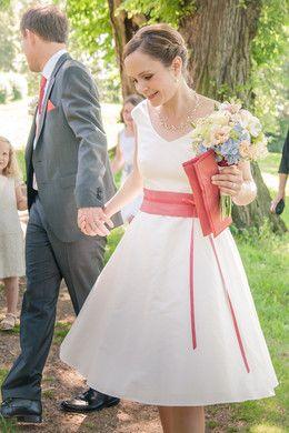 knielanges junges Hochzeitskleid mit V- Ausschnitt und rosa- koralle Gürtel mit kleiner Schleife und passender Tasche für die Braut (http://www.noni-mode.de)