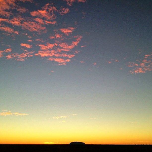 Beautiful view of Uluru in the distance at sunrise.