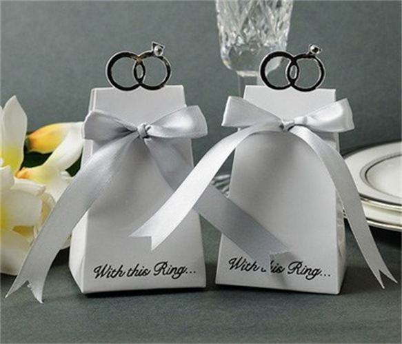 "SIMPLE FAVOURS BOMBONIERE - Wedding Favours    With This Ring Wedding Favor Boxes with Ribbon - White  SOLD IN LOTS OF 10 Celebrating the significance and beauty of the rings you said  ""I Do"" with today, this unique favor box sparkles with love.  Size: 6.35cm x 5.1cm x 12cm Boxes come flat, easy to assemble. Silver Ribbons are INCLUDED!  Price: $13.50"