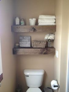 A couple of thick wooden beam floating shelves flanked in a corner of a beige-colored wall adds flair to an otherwise ordinary-looking bathroom.