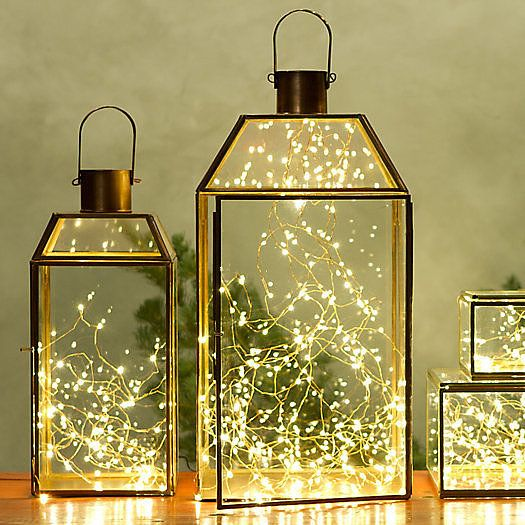 Fill glass lanterns with delicate tangles of lights instead of candles. Image Source: Terrain