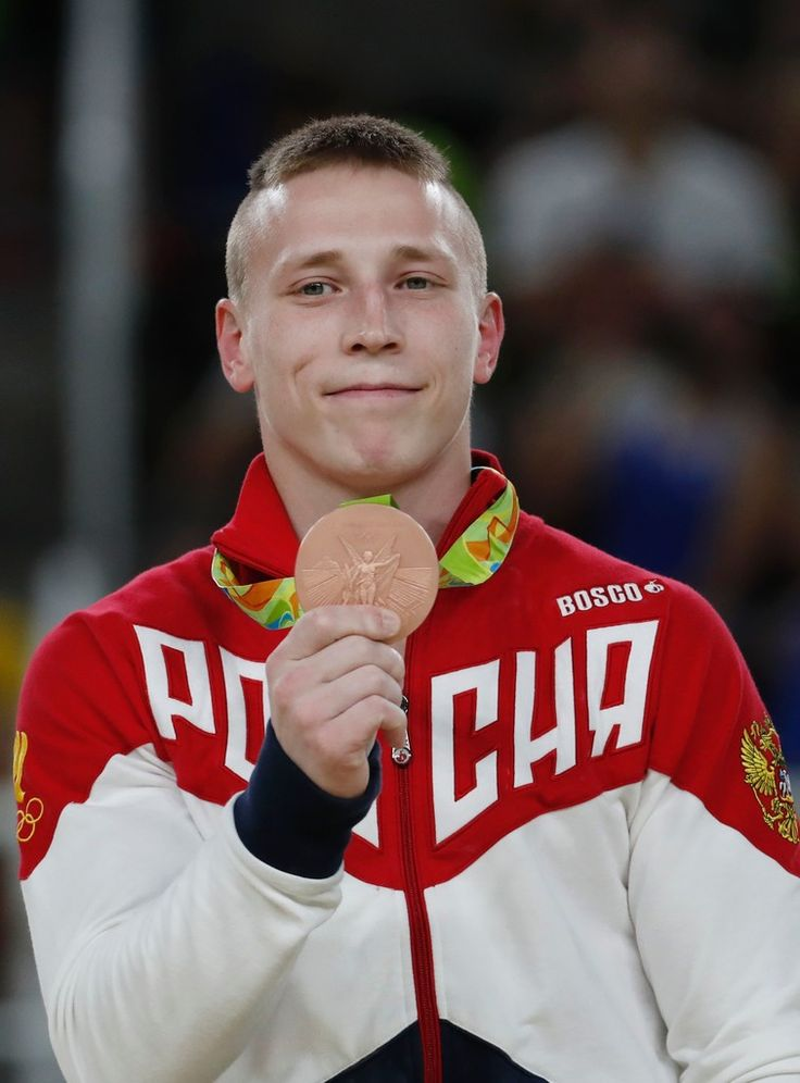 Bronze medallist Russia's Denis Abliazin poses on the podium of the men's rings event final of the Artistic Gymnastics at the Olympic Arena during the Rio 2016 Olympic Games in Rio de Janeiro on August 15, 2016. / AFP / Thomas COEX