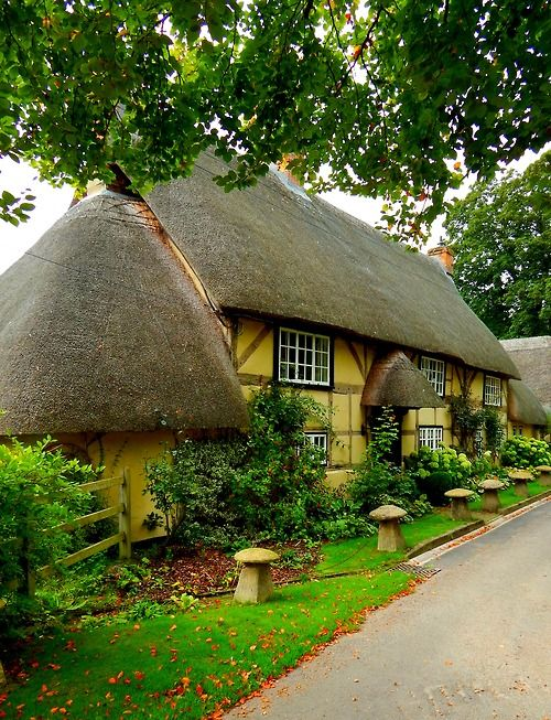 Charming yellow cottage with thatched roof.