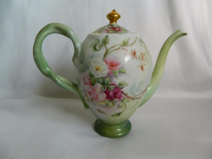 This auction item is a Lovely Antique Limoges Porcelain Teapot. It is beautifully painted with Pink and Red Roses and vines on a Pale Green background. The roses and foliage are continued on the back