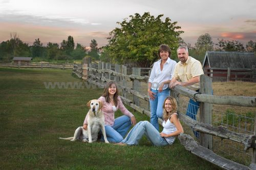 family Of Four And Their Dog Posing Next To A Fence
