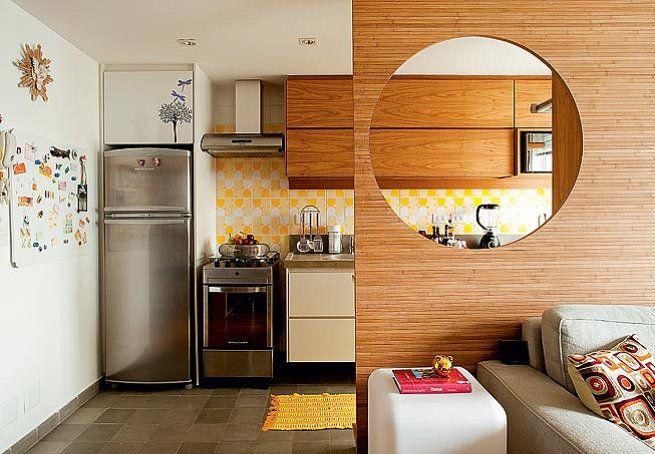 Tudo integrado. Essa é a proposta do apê, que tem cozinha com piso de ladrilhos hidráulicos. A partir da sala, o destaque é o painel de bambu prensado com o elemento circular vazado