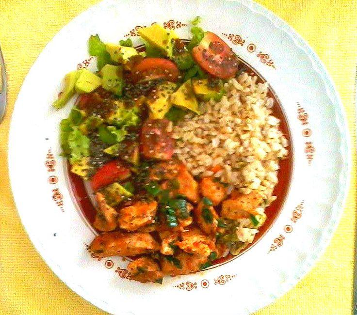 Nutrição com alimentos integrais e orgânicos. Frango com molho de tomate caseiro, arroz integral com brócolis e cenoura, e salada de tomate cereja, alface e abacate com chia.