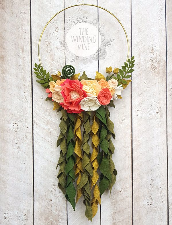"""This wreath is a perfectly lovely addition to your door or décor for any room. The 10"""" metal ring wreath is embellished with a cluster of handmade wool-blend flowers, leaves, fronds, and curly fiddleheads. You'll find baby mums, peonies, roses, and other flowers in various shades of peach and coral. There are seven vines of hanging leaves below the flower cluster. Each wreath is made by hand with love in my smoke-free home. All of The Winding Vine products are created with wool-blend felt…"""