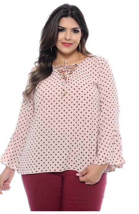 1822fa933 Blusa Plus Size confeccionada em Crepe Bubble de poá com fundo rosa. O  decote é em V com detalhe de amarração e a manga é estilo