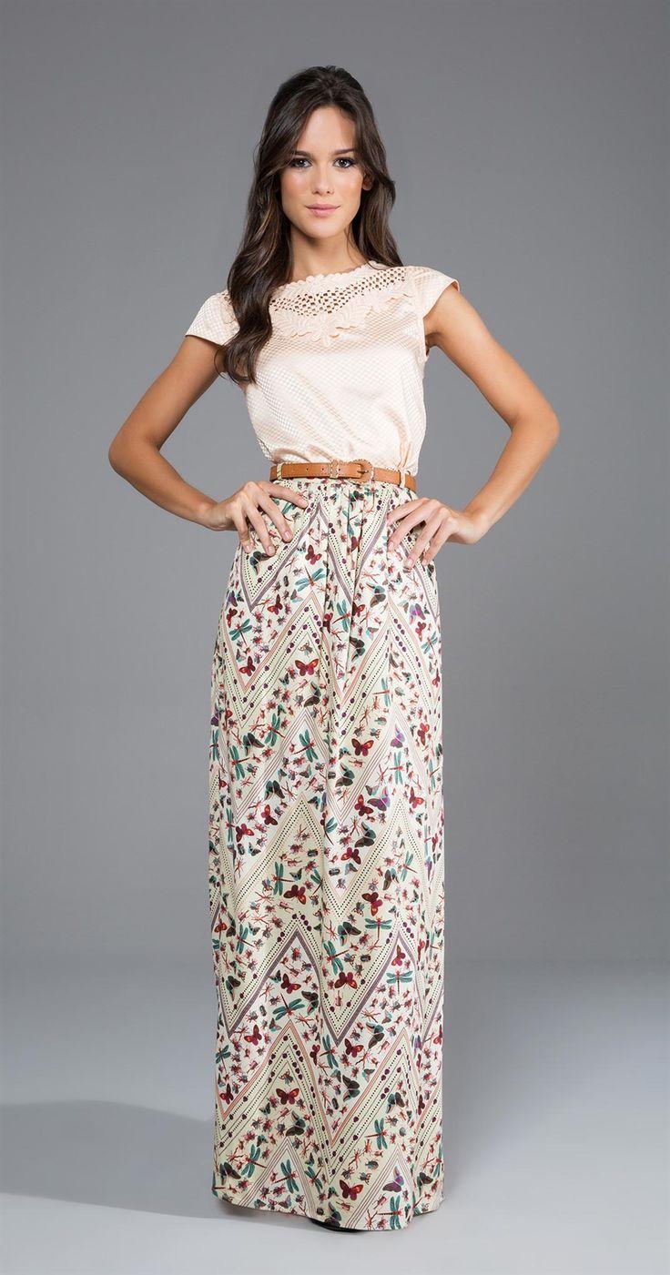 Outfit estilo romántico, falda larga con flores de tela suave, con colores primaverales, con un blusa blanca con ligero bordado, el cabello suelto con ondas.