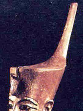 A outra era um barrete achatado, prolongando-se na parte posterior por um apêndice alto e com uma tira metálica enrolada na ponta e voltada para a parte frontal da coroa. Ambas já aparecem sendo usadas por Narmer (c. 3000 a.C.) na sua paleta. Por sua vez, a vermelha já surge numa representação em relevo em um caco de vaso do período pré-dinástico. Tal fragmento foi encontrado na região do Alto Egito, de onde parece que a coroa se originou, embora tenha se tornado posteriormente símbolo do…