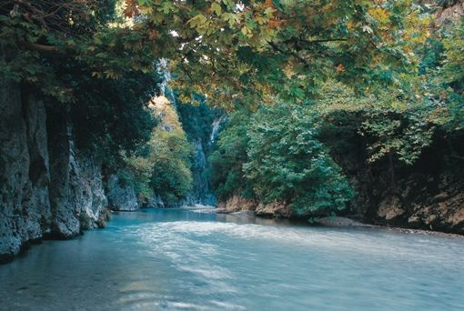 "VISIT GREECE| Acherontas river, the mythical river of Epirus.  Dominated by nuances of green, exciting paths stretch along the river; at times they cross it, as they tread on arched rocky bridges. At a certain point the river narrows between green-clad steep high cliffs that seem to be forming an enormous gate through which the water of the river rushes fiercely; no wonder the legendary name of the spot is ""The Gate to the Underworld""."