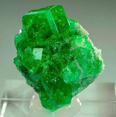 Tsavorite garnets on graphite matrix!From Merelani Mine, Arusha, Tanzania. Credit: Anton Watzl Chrome grossular is a green variety of grossular. Tsavorite (or tsavolite) is a grossular that, like the Meralani mint, is green in colour. It is coloured by chromium and/or vanadium. The distinction between a 'regular' green grossular and tsavorite is commonly thought to be a function of saturation and tone.