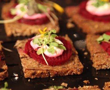 Pumpernikel, rodaja de remolacha, queso de cabra y micro hierbas