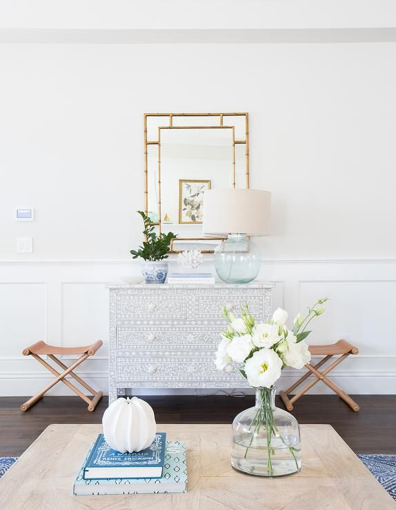 Chic foyer features a wall lined with wainscoting lined with a black and white bone inlay chest ...