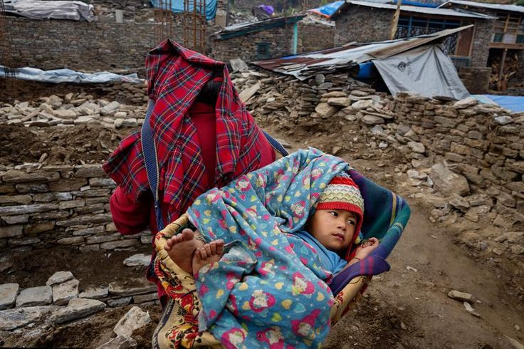 A woman carries a child among wreckage in the village of Barpak, Nepal  in Gorkha district, at the epicenter of the 2015 quakes, April 3, 2016.