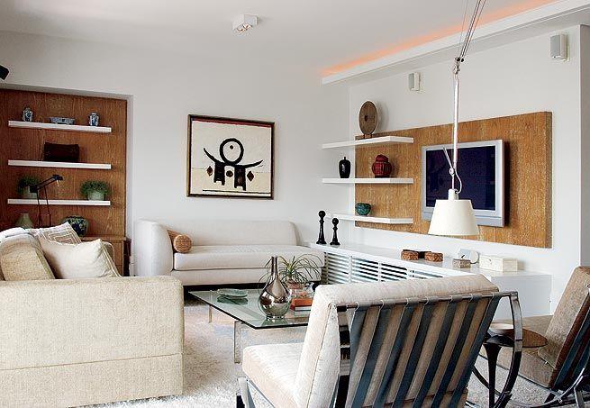 Sala com duas estantes, que se combinam e têm materiais e desenhos parecidos: fundo de madeira e prateleiras de laca branca. Via Casa e Jardim.