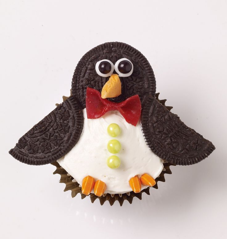 We've made penguin cupcakes before--but never one this easy or this much fun! They're the COOLEST. Here's how we made them: Start with vanilla cupcakes. (We like to make them in foil liners.) Frost...