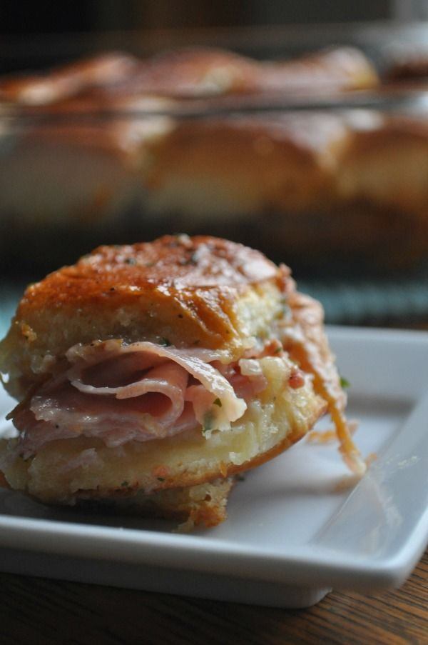 These delicious baked ham sandwiches don't need to be individually made...you just put the whole giant container of sweet rolls in the bottom of a baking dish, cut in half...and work from there.  Genius!