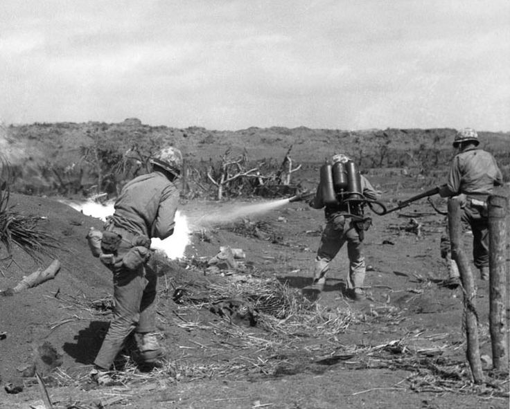 A US Marine used a flamethrower against a Japanese pillbox as he was covered by two riflemen, Iwo Jima, Feb 1945