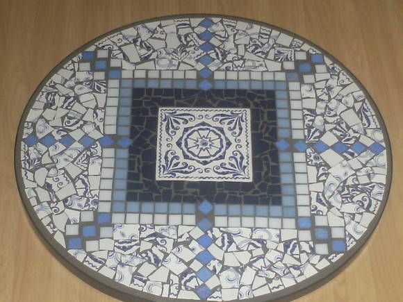Tampo de mesa feito co pastilhas, azulejo portugues e,  pedaços do mundo de azulejos azul. Técnica indireta, para ambiente internos ou externos. Com espera para pés.