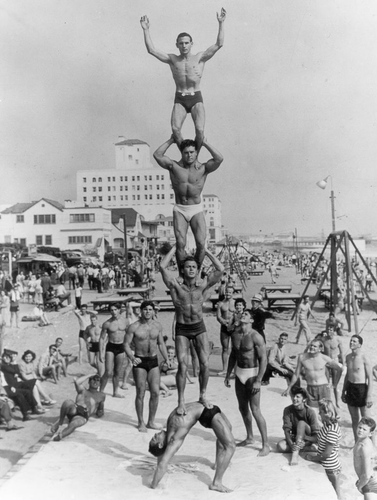 """Muscle Beach, Santa Monica, California, 1934.  Bottom: Harold Zinkin - Inventor of Universal Gym Equipment, 1st Mr. California, U.S. National Weightlifting Champion.  On top of Harold: DeForest Most (known as """" Moe"""") - Original Sports Director of Muscle Beach.  On top of Moe: Jack LaLanne - Godfather of Fitness.  On top of Jack: Gene Miller - Professional Hand Balancer."""