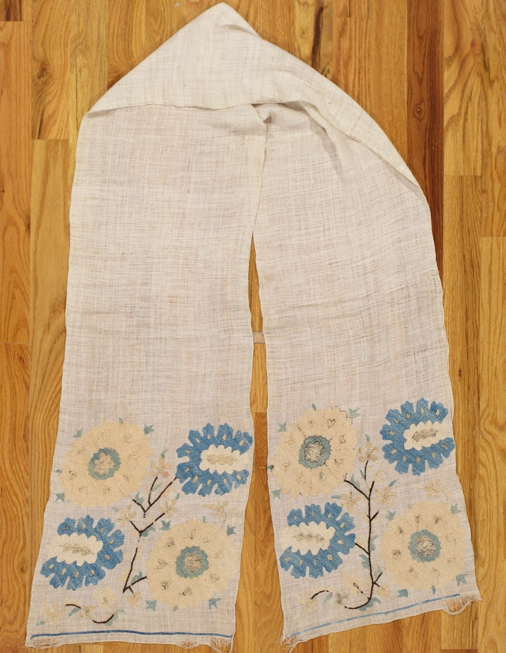 Ottoman textile,Western Anatolia,circa 1800.Dimensions:6.8x1.0 ( 203x30 cm).Silk embroidery on linen.Each end contains four large flowers in light blue and light yellow growing from a dark brown stem.There are small details in metal threads.The center is plain and the piece is finely woven.It was probably used as a hand towel in an affluent household.The colors are good and the piece is in good condition.