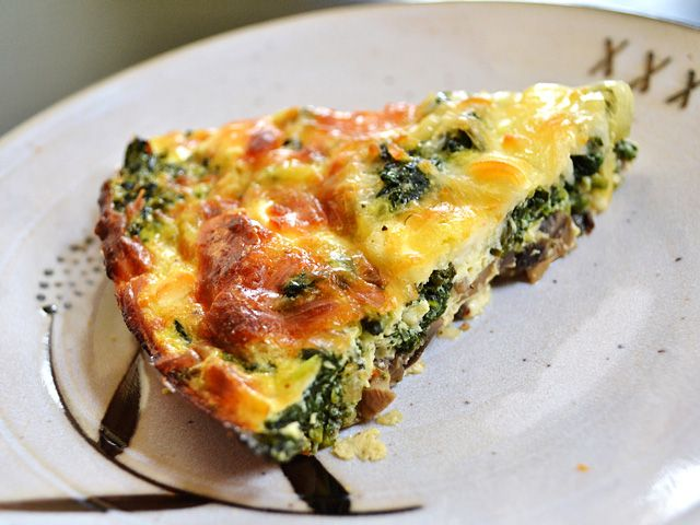 This easy and delicious Spinach Mushroom Crustless Quiche is low on carbs and big on flavor. This veggie filled breakfast will keep you full and happy. BudgetBytes.com slice