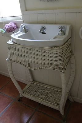 .Old sink in vintage wicker table. Love it!