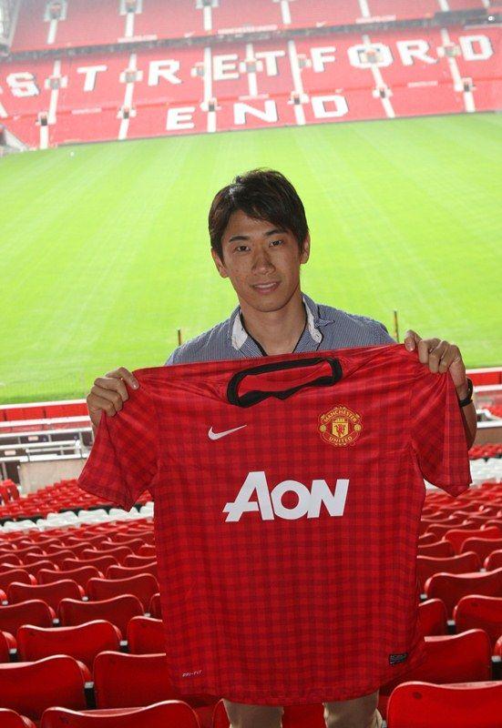 shinji kagawa poses in the Old Trafford's stand