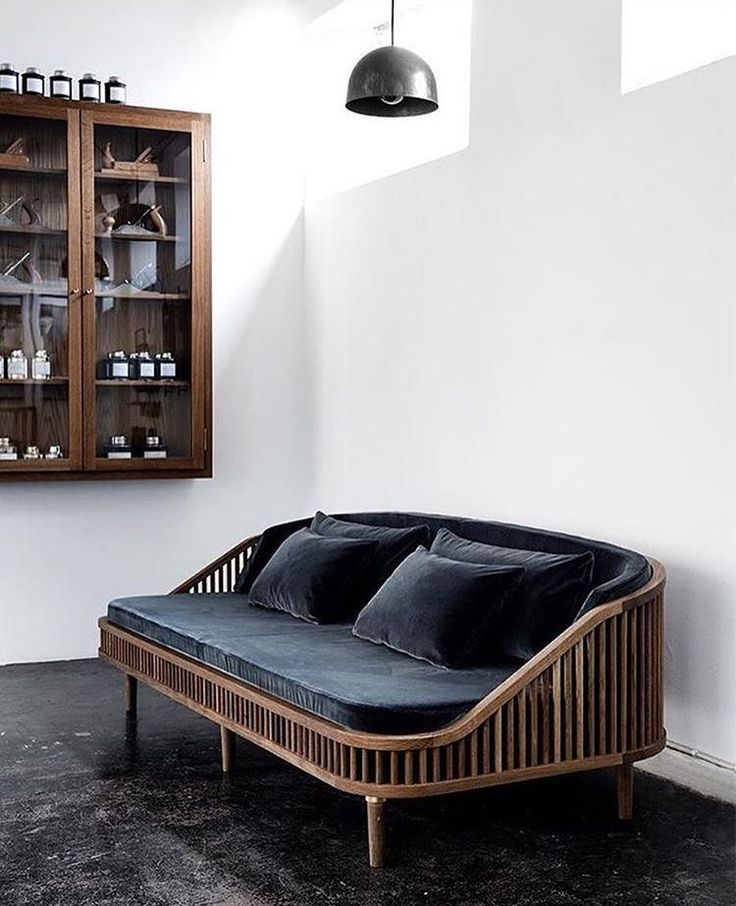 blue velvet sofa with wood frame and glass wall-hung cabinet