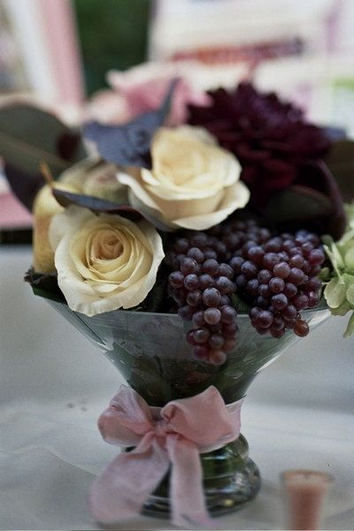 Deep purple centerpieces for wedding. Great way to incorporate something unique with adding fruit to your arrangements.