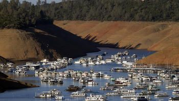 hundreds of houseboats dwarfed by steep banks that show the water level down 160 feet from the high water mark at Bidwell Canyon Marina on Lake Oroville on June 21. #Californiadrought