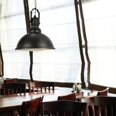 Metal pendant lamp in graphic grey over a dining table in a restaurant.