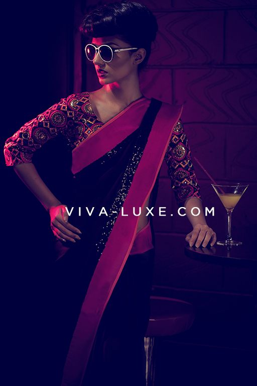 VIKRAM PHADNIS  Bold, satin georgette saree in jet black with stunning pink/orange raw silk borders. Features black sequin work throughout. Contrasting semi-stitched, raw silk blouse with 3/4 length sleeves included.  Blouse is fully embroidered in multi-coloured resham thread work with antique gold sequins. #Saree #Designer #VIVA-LUXE #Bollywood #Indianfashion