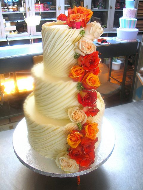 3-tier Wicked Chocolate wedding cake iced in spanish textured white ganache decorated with fresh cream & burnt orange roses by Charly's Bakery, via Flickr
