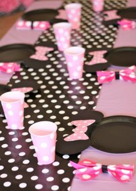 ミニーマウスがテーマのパーティーのテーブル。ピンクのビニールの使い捨てテーブルクロスに、モノクロの水玉のラッピングペーパーをテーブルランナー代わりに使用。ミニー型の紙皿は黒の紙皿に色画用紙で作った耳とリボンをつけて、ピンクのカトラリーとピンク&白の水玉のナプキンと紙コップで簡単かつ安上がり、でもお金をあまりかけていないようには見えない!
