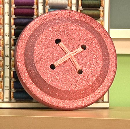How to make Big Buttons with Mark Montano  > using Frisbees, yarn, spray-paint & a drill ...how easy!  Have also seen this done with paper plates if someone doesn't happen to have a drill to go through the plastic Frisbees.   Cute idea for sewing or crafts room.