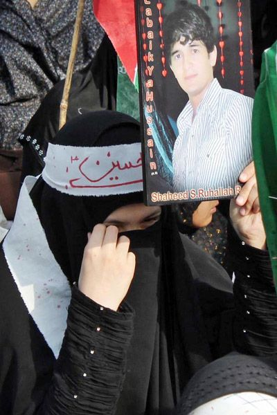 LAHORE: Apr10 – Woman carrying a picture of her relative during a demonstration by Imamia Students Organization against target killing in Gilgit outside press club.