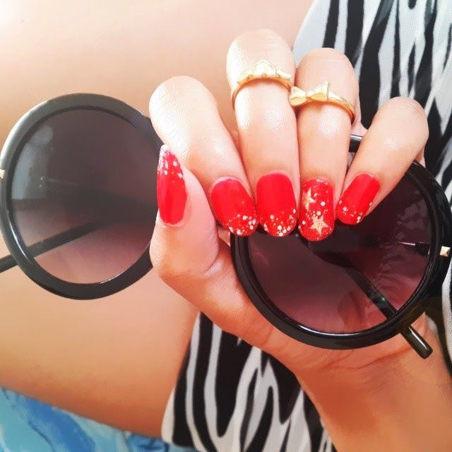 Red and Gold Glitter and Stars (Christmas Nails) with black Round framed statement sunglasses and midi rings.