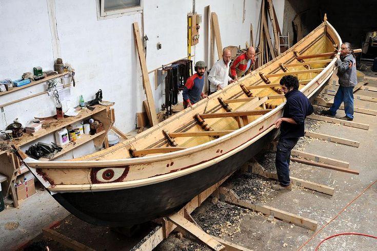 """Construction du bateau grec """"Gyptis"""", travaux d'étanchéité à l'aide de goudron de bois à l'extérieur, et de cire d'abeille à l'intérieur."""